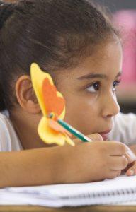 Foto: Menina com lápis na mão prestando atenção na aula