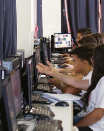 Foto: vários adolescentes estudando em laboratório de informática
