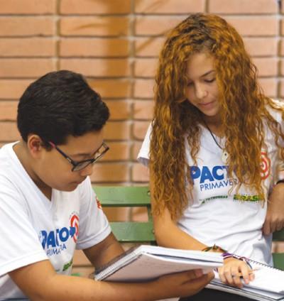 Foto: Um rapaz e uma moça estudando juntos