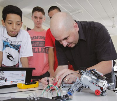 Foto: Professor e três alunos desenvolvendo projeto de robô